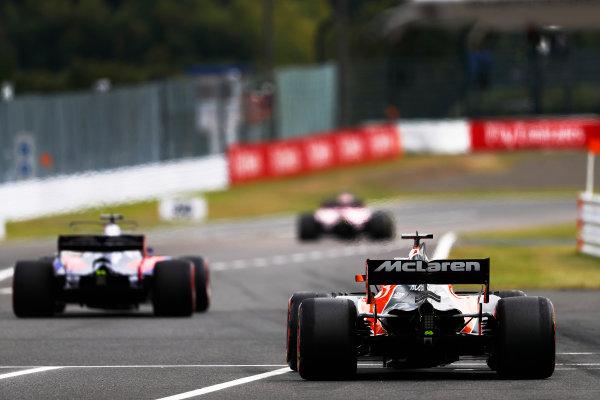 Suzuka Circuit, Japan. Saturday 07 October 2017. Fernando Alonso, McLaren MCL32 Honda, and Pierre Gasly, Toro Rosso STR12 Renault, leave the pits. World Copyright: Glenn Dunbar/LAT Images  ref: Digital Image _31I6771