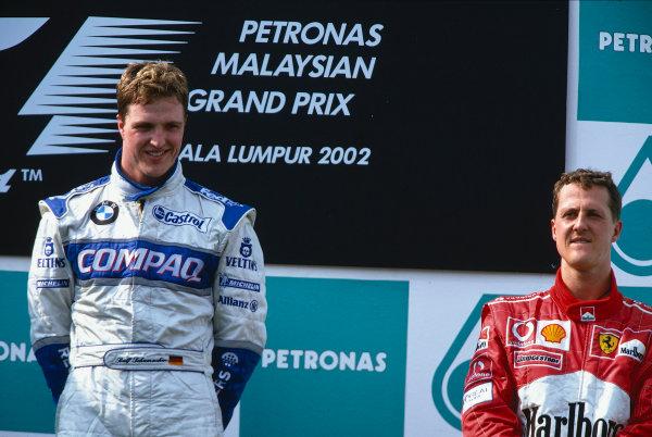 2002 Malaysian Grand PrixSepang, Malaysia. 15th - 17th March 2002.Race winner Ralf Schumacher, BMW Williams FW24, with brother Michael Schumacher, Ferrari F2001, (3rd) podium .World Copyright: Steven Tee/LAT Photographicref: 35mm Image A65