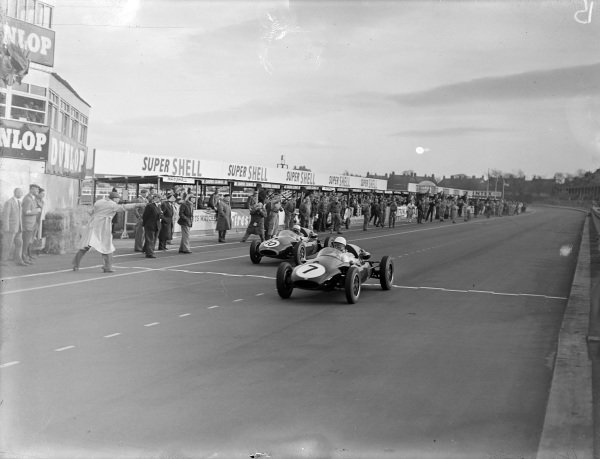 Stirling Moss, Cooper-Climax T45, leads Jack Brabham, Cooper-Climax T45, across the line and takes the chequered flag.