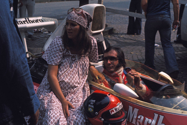 Emerson Fittipaldi, McLaren M23 Ford, with his wife sitting on the car next to him.