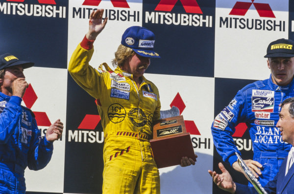 Keke Rosberg, 1st position, celebrates on the podium as his hand bleeds. Beside him is Jacques Laffite, 2nd position, and Philippe Streiff, 3rd position.