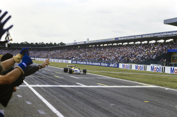 The Williams team celebrates as Nelson Piquet, Williams FW11B Honda, takes the chequered flag.