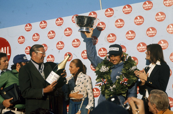 Carlos Reutemann celebrates victory on the podium.