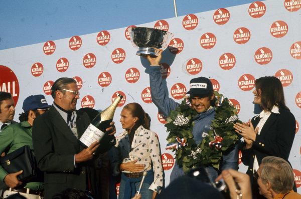 Carlos Reutemann celebrates victory on the podium.