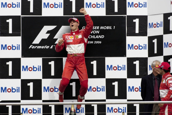 Michael Schumacher jumps in celebration of his victory on the podium.