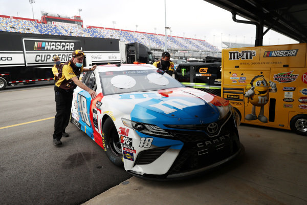 The crew push the #18 M&M's Toyota,  driven by Kyle Busch through the garage Copyright: Chris Graythen/Getty Images.