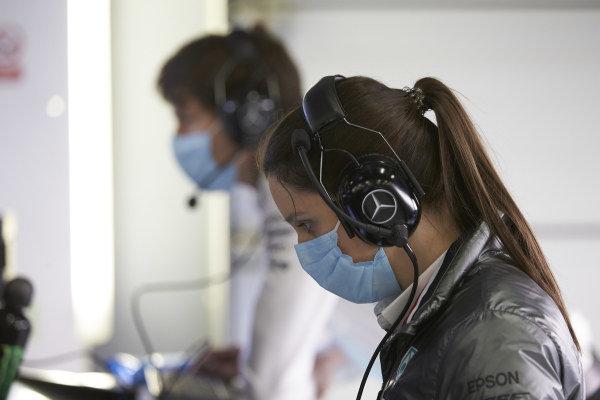 Mercedes team member wear protective masks in the garage