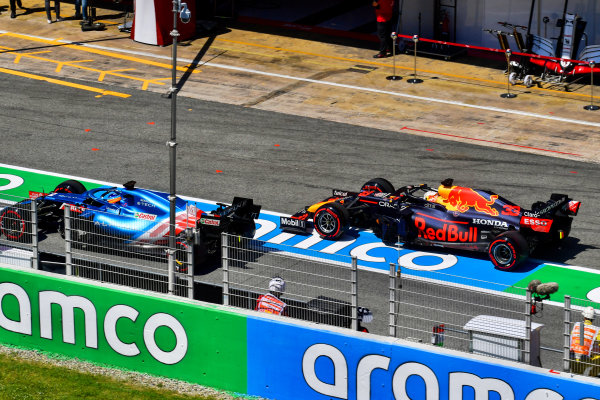 Fernando Alonso, Alpine A521, leads Max Verstappen, Red Bull Racing RB16B, in the pit lane