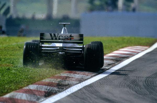 Sepang, Kuala Lumpur, Malaysia. 15-17 October 1999. McLaren MP4/14 Mercedes runs wide onto the grass. Action. Ref: 99MAL17. World Copyright - LAT Photographic