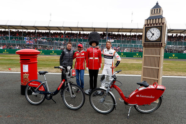 Silverstone, Northamptonshire, UK.  Thursday 13 July 2017. Stoffel Vandoorne, McLaren, MarcGene of Ferrari and Jenson Button, McLaren, with a dummy Scots Guard and bicycles. World Copyright: Glenn Dunbar/LAT Images  ref: Digital Image _X4I2786