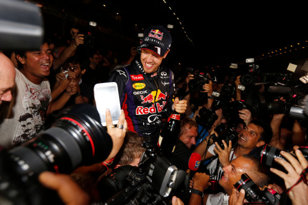 Buddh International Circuit, New Delhi, India. Sunday 27th October 2013. Sebastian Vettel, Red Bull Racing, 1st position, celebrates with fans after securing fourth drivers world title. World Copyright: Charles Coates/LAT Photographic. ref: Digital Image _N7T5903