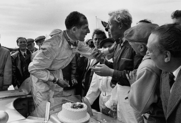Dundrod, Northern Ireland, Great Britain. 17th September 1955. Mike Hawthorn eats Stirling Moss's birthday cake after the race. Moss, Mercedes-Benz 300SLR finished in 1st position with John Fitch, portrait. World Copyright: LAT Photographic Ref: Autosport b&w print. Published: Autosport, 23/9/1955 p369