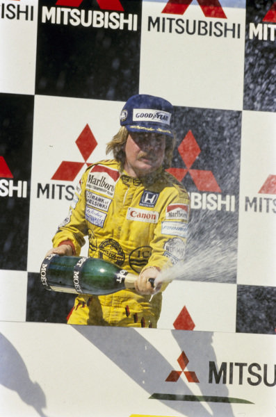 Keke Rosberg, celebrates winning on his final appearance for Williams on the podium.