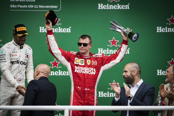 Kimi Raikkonen, Ferrari, 3rd position, lifts his trophy