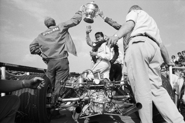 Jim Clark celebrates victory with his mechanics and Lotus 49 Ford.