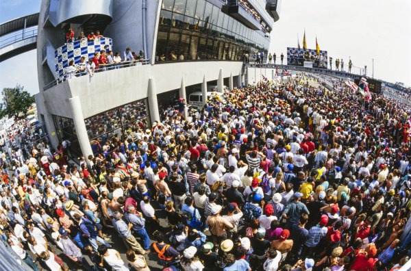 Fans fill the pitlane as the drivers celebrate on the podium.