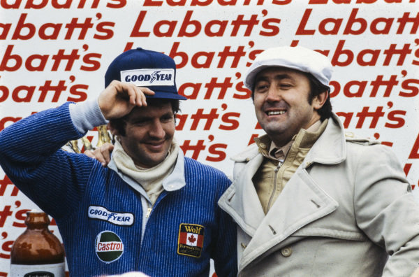Jody Scheckter and team boss Walter Wolf celebrate victory on the podium.
