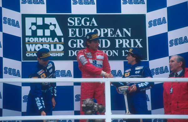 1993 European Grand Prix. Donington Park, England. 9-11 April 1993. Ayrton Senna (McLaren Ford) 1st position is congratulated by Alain Prost (Williams Renault) 3rd position. Damon Hill (Williams Renault) 2nd position also on the podium.  Ref-93 EUR 12. World Copyright - LAT Photographic