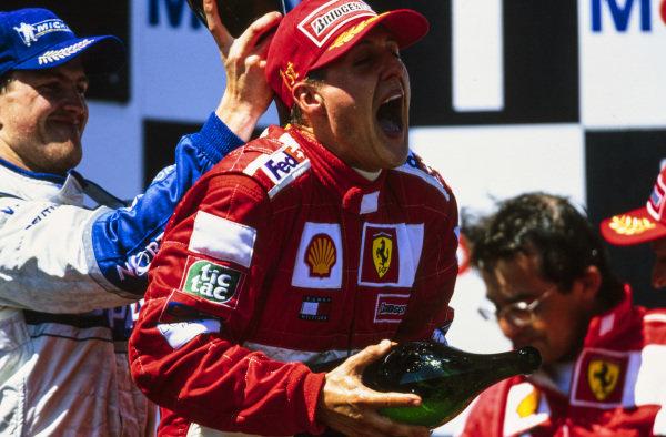 Michael Schumacher, 1st position, celebrates on the podium with Ralf Schumacher, 2nd position.
