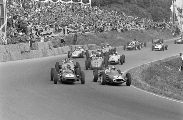 Bruce McLaren, Cooper T53 Climax, battles with Innes Ireland, Lotus 21 Climax, at the start. They lead Hans Herrmann, Porsche 718, Dan Gurney, Porsche 718, Stirling Moss, Lotus 18/21 Climax, Jack Brabham, Cooper T53 Climax, and Edgar Barth, Porsche 787.
