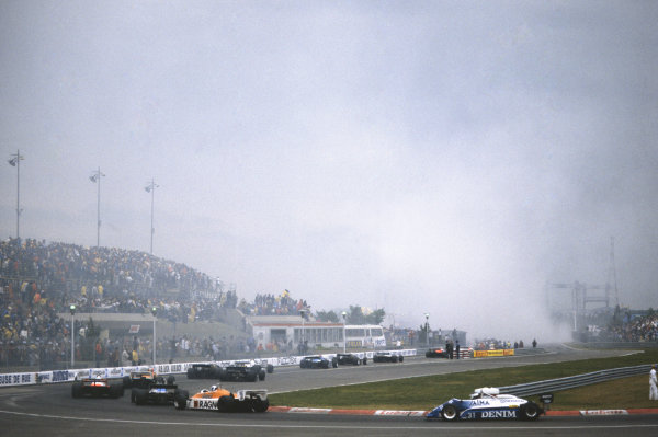 1982 Canadian Grand Prix  Montreal, Quebec, Canada. 11-13th June 1982.  Cars return to the pits as smoke rises from the startline accident in which Riccardo Paletti lost his life.  Ref: 82CAN09. World copyright: LAT Photographic