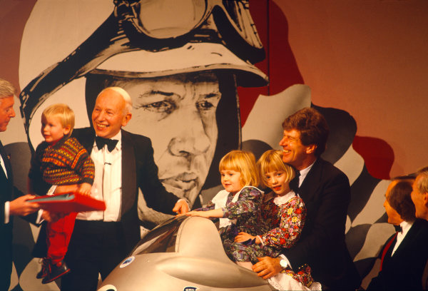 Grosvenor House Hotel, Park Lane, London. 6th December 1992.John Surtees receives his This Is Your Life red book from Michael Aspel on the stage at the Autosport Awards evening. He is carrying his son Henry, whilst his two daughters look on.World Copyright: LAT Photographicref: 35mm Transparency Image