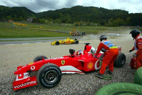 Rubens Barrichello (BRA) Ferrari F2002 climbs from his car as Giancarlo Fisichella (ITA) Jordan Honda EJ12 spins into the gravel in sympathy. Austrian Grand Prix, A1-Ring, 10 May 2002. DIGITAL IMAGE