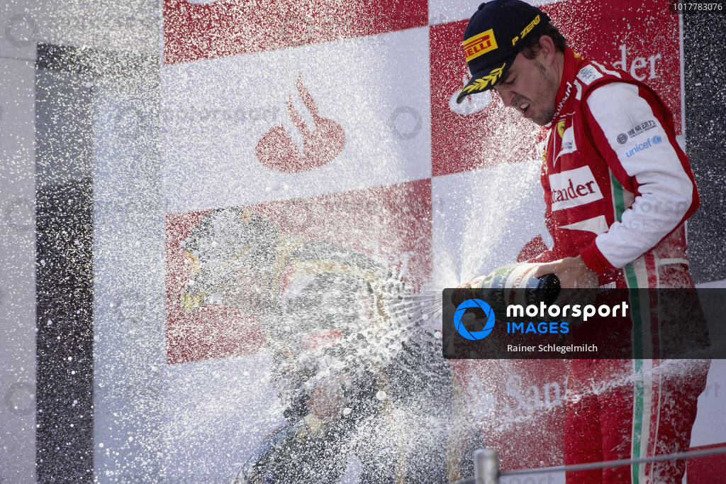 Fernando Alonso, 1st position, celebrates what would turn out to be his final grand prix win on the podium with Kimi Räikkönen, 2nd position.