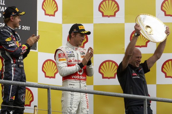Adrian Newey celebrates on the podium alongsideSebastian Vettel, 1st position, and Jenson Button, 3rd position.