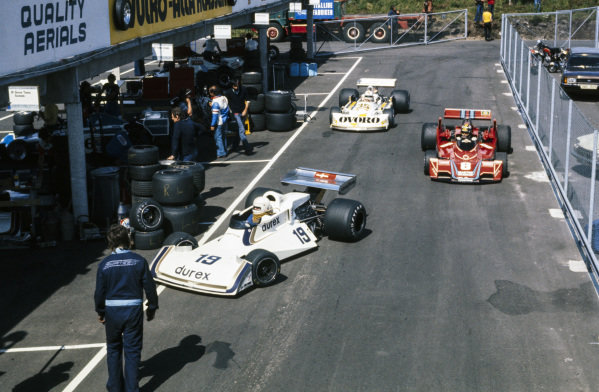 Alan Jones, Surtees TS19 Ford, Carlos Pace, Brabham BT45 Alfa Romeo and Arturo Merzario, March 761 Ford enter the pitlane.