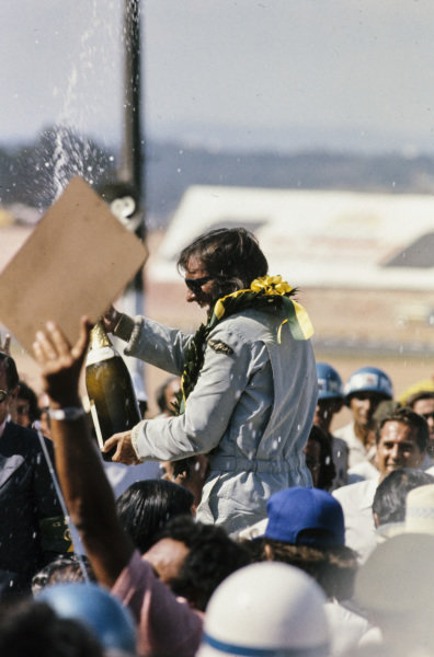 Emerson Fittipaldi celebrates victory on the podium with a bottle of champagne.