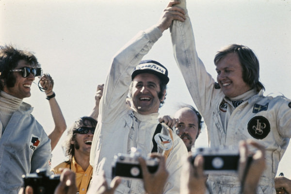 Winner Denny Hulme congratulates home driver Ronnie Peterson on his second place as François Cevert looks on.