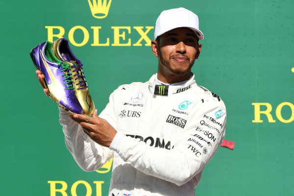 Race winner Lewis Hamilton (GBR) Mercedes AMG F1 celebrates on the podium with the running shoes of Usain Bolt (JAM) at Formula One World Championship, Rd17, United States Grand Prix, Race, Circuit of the Americas, Austin, Texas, USA, Sunday 22 October 2017. BEST IMAGE