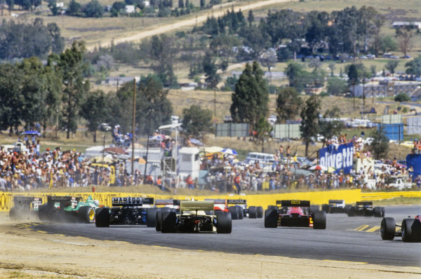 The field on the first lap. The Alfa Romeo 184T pair of Riccardo Patrese and Eddie Cheever make contact.