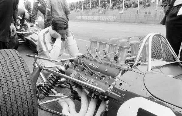 Jim Clark examines the rear of his Lotus 49 Ford.