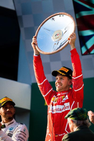 Race winner Sebastian Vettel (GER) Ferrari celebrates on the podium with the toprhy at Formula One World Championship, Rd1, Australian Grand Prix, Race, Albert Park, Melbourne, Australia, Sunday 26 March 2017.