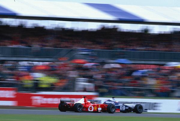 2002 British Grand Prix, Silverstone, England. 7th July 2002. Rubens Barrichello cuts inside Juan Pablo Montoya as the cars run through Woodcote.World Copyright - LAT Photographic Ref: 35mm Original A01