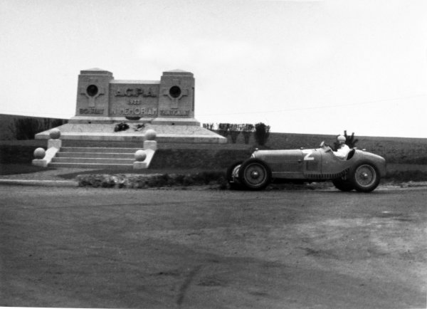 "1935 Picardie Grand Prix Peronne, France. 26 May 1935 Raymond Sommer, Alfa Romeo Tipo-B ""P3"", 3rd position, passes the memorial to Louis Trintignant (father of Maurice) and Guy Bouriat at Mons-en-Chaussee, where both had been killed in 1933. Action World Copyright: Robert Fellowes/LAT PhotographicRef: 35PIC04"