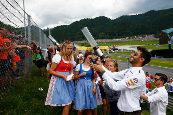 Red Bull Ring, Spielberg, Austria. Sunday 09 July 2017. Daniel Ricciardo, Red Bull Racing, fires T-shirts into the crowd as glamorous Austrian girls in dirndls look on. World Copyright: Andy Hone/LAT Images ref: Digital Image _ONY2476