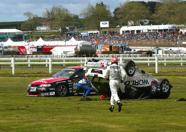V8 SUPERCAR drivers race to help Jason Richards after he rolled his Holden Commodre at the end of the first practice session at Pukekohe raceway 40km south of Auckland, New Zealand 07/11/03.