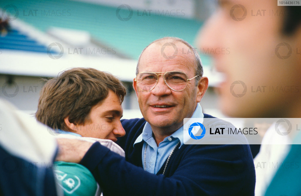 1984 Formula One World Championship. Guy Ligier hugs Eddie Cheever in the pits, portrait.  World Copyright: LAT Photographic.