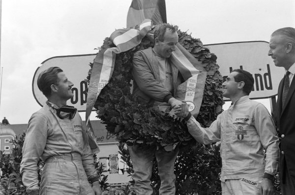 John Surtees, 1st position, celebrates on the podium, with Graham Hill, 2nd position, and Lorenzo Bandini, 3rd position, with whom Surtees shakes hands with.