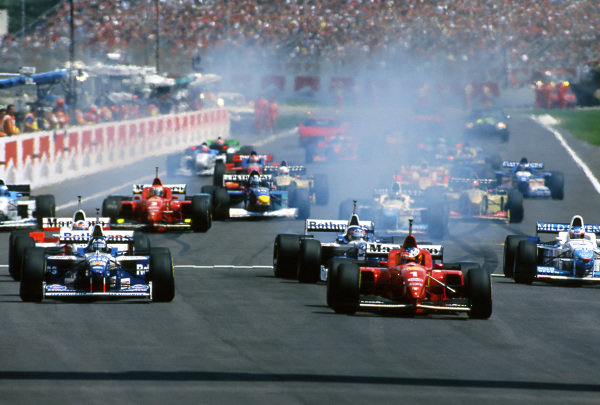 Michael Schumacher (GER) Ferrari F310 leads Damon Hill (GBR) Williams FW18 at the start of the race at Formula One World Championship, San Marino Grand Prix, Rd5, Imola, Italy, 5th May 1996.