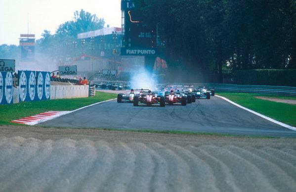 1994 Italian Grand Prix.Monza, Italy.9-11 September 1994.Jean Alesi leads teammate Gerhard Berger (both Ferrari 412T1B's) with Johnny Herbert (Lotus 109 Mugen-Honda) behind at the start.Ref-94 ITA 04.World Copyright - LAT Photographic