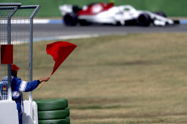 A marshal waves a red flag as Charles Leclerc, Sauber C37 Ferrari, passes by.