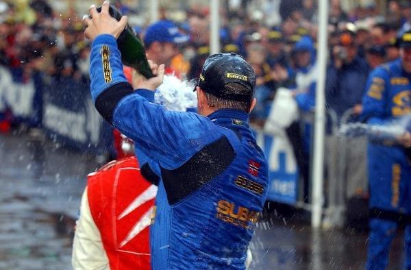 (L to R): Rally winner Petter Solberg (NOR) Subaru celebrates by spraying second place finisher Sebastien Loeb (FRA) Citroen with champagne.World Rally Championship, Rd10, Telstra Rally Australia, Day Three, Perth, Australia, 7 September 2003.DIGITAL IMAGE