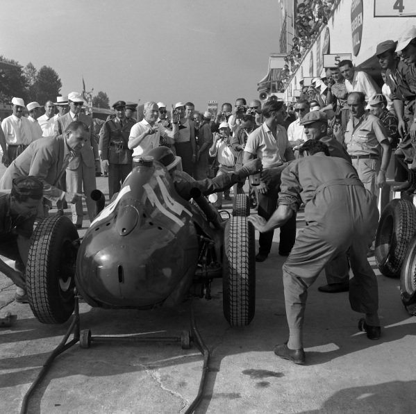 Mike Hawthorn, Ferrari 246, takes some refreshment during a pitstop.