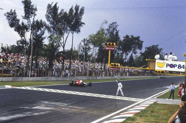 Alain Prost, McLaren MP4-4 Honda, crosses the line and takes the chequered flag.