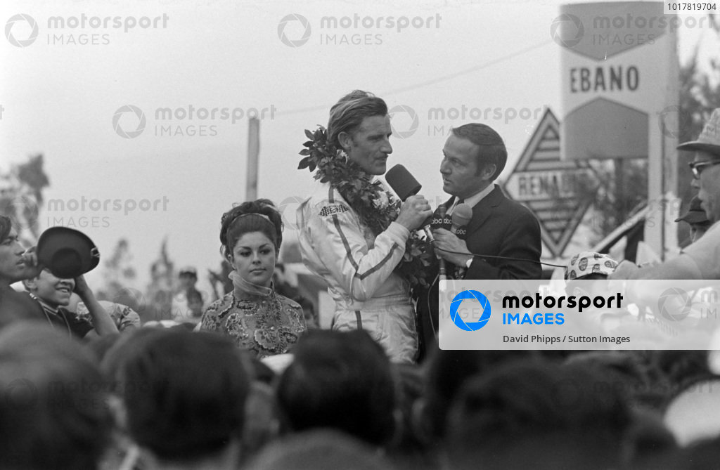 Graham Hill, 1st position, is interviewed on the podium.
