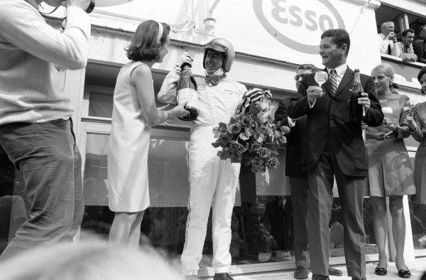 Race winner Jack Brabham celebrates on the podium.
